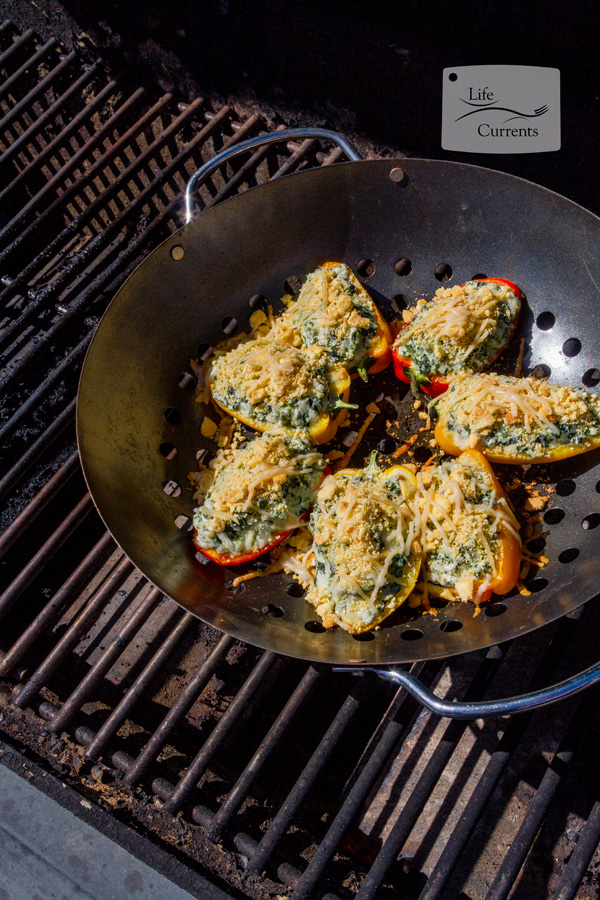 Grilled Cheesy Spinach Dip Stuffed Peppers on the grill, topped with cronbread topping and Parmesan cheese