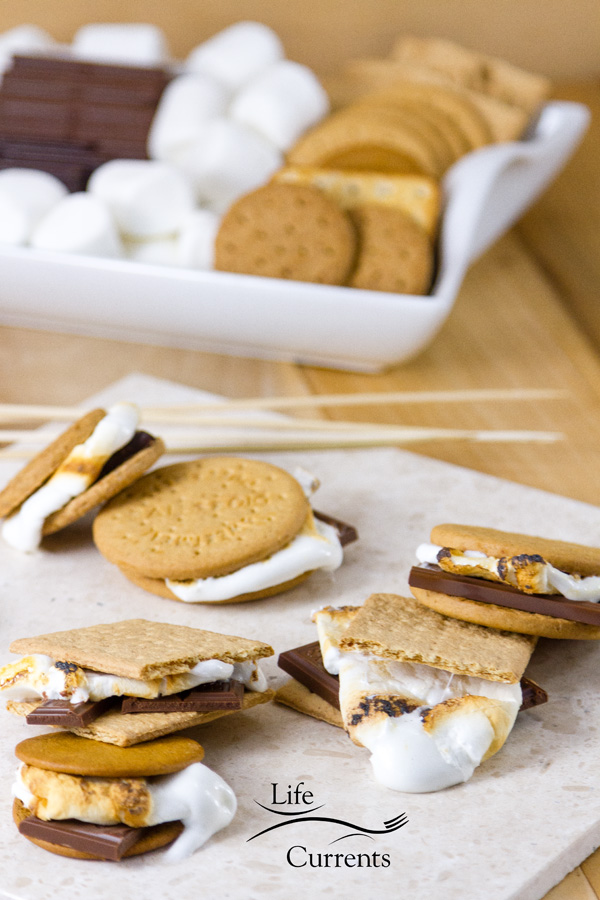 Gourmet s'mores in the foreground with the s'mores tray filled with supplies in the background