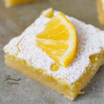 close up on a lemon bar slice with a lemon garnishing the top