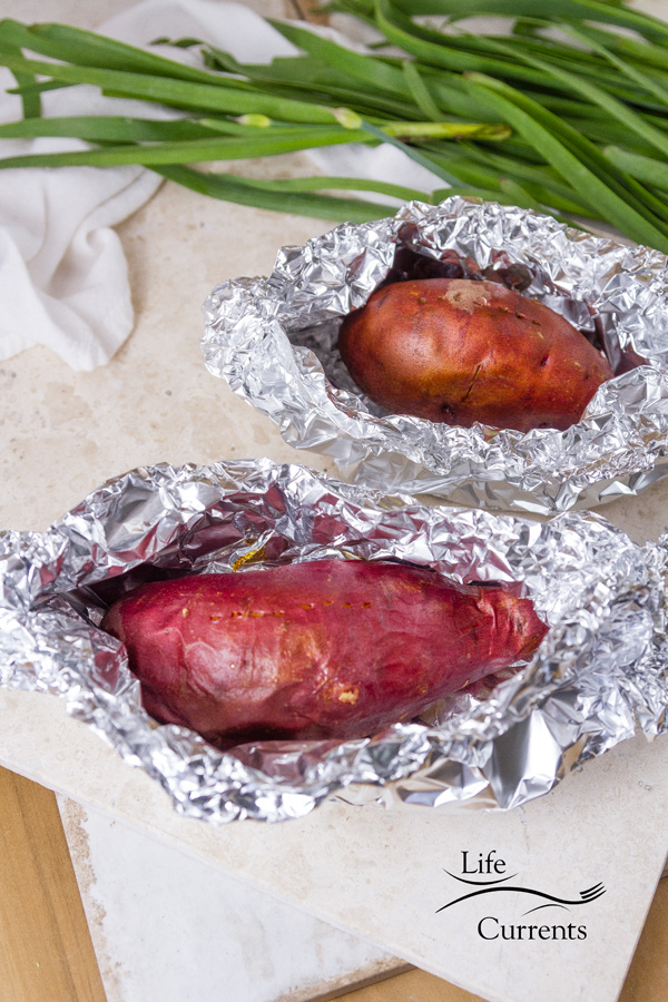 Baked sweet potatoes in foil on a white background with chives in the picture
