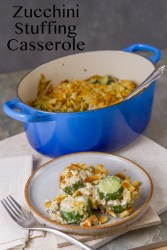 Zucchini Stuffing Casserole in a blue casserole dish with a serving in front on a white plate with a fork and a white napkin on a grey background