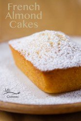 One Financier (French Almond Cake) dusted with powdered sugar on a white plate