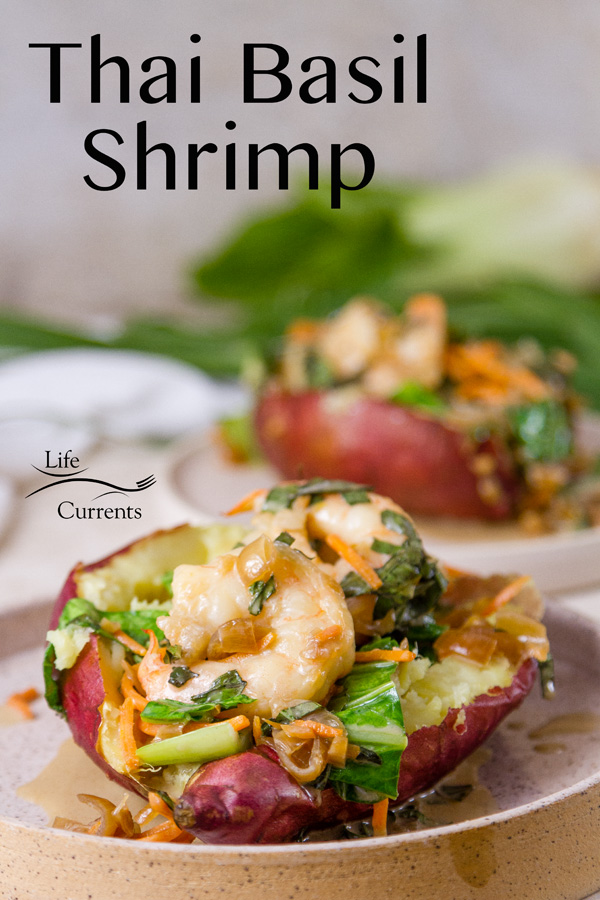 Thai Basil Shrimp with stir fried veggies in a baked sweet potato, two servings, on whit plates with bok choy and chives in the background
