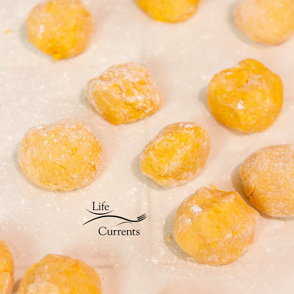 Uncooked sweet potato rice balls on parchment paper