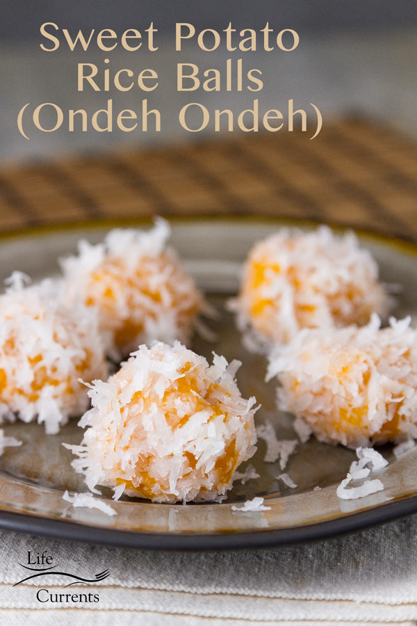 Sweet Potato Rice Balls in coconut (Ondeh Ondeh) on a grey plate with an Asian mat in the background
