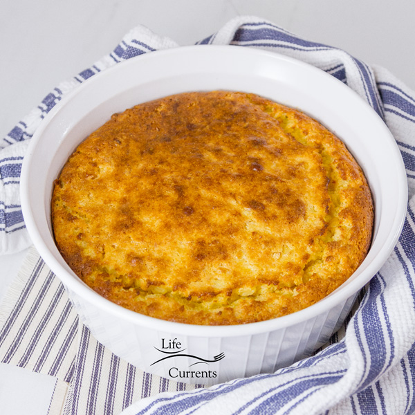 corn casserole baked in a white casserole dish on a blue striped cloth