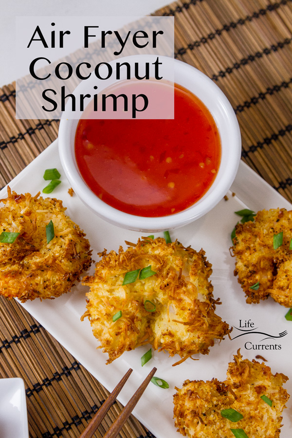 Air Fryer Coconut Shrimp on a white plate with a red dipping sauce on a wooden mat with a title
