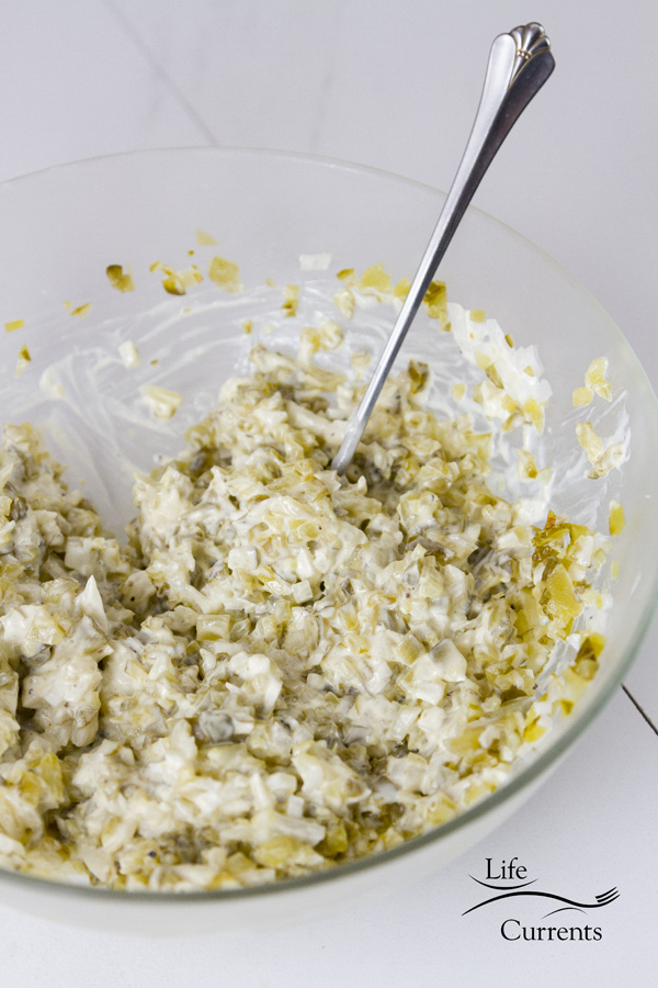Potato Salad dressing in a glass bowl with a spoon on a white background