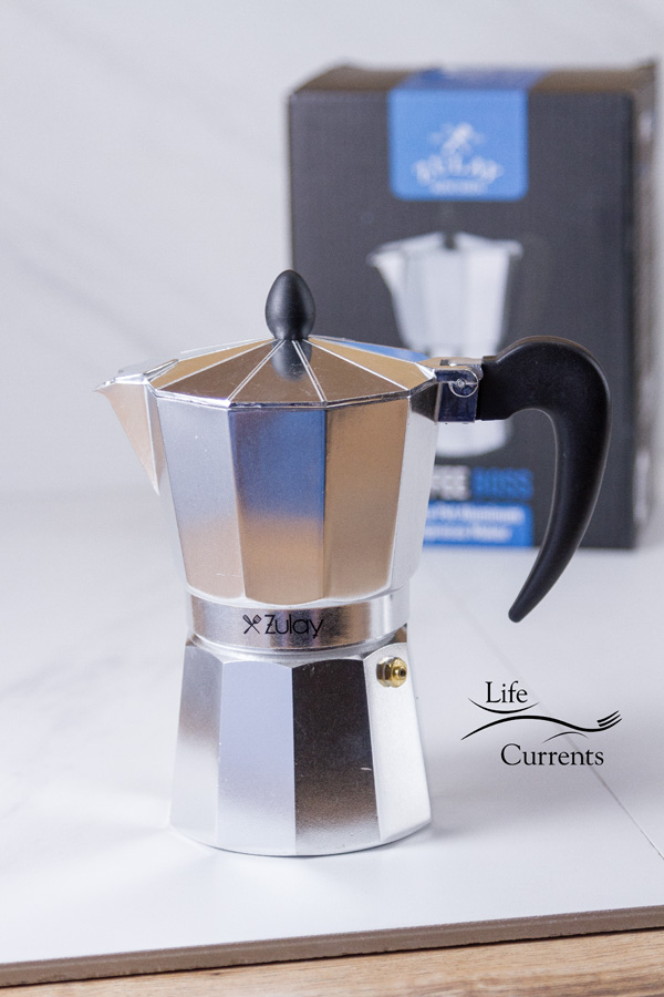 A Zulay Stovetop espresso maker on a white tile background with the box in the back