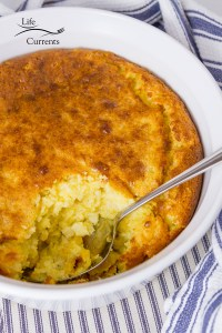 corn casserole with a serving taken out on a blue cloth