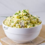 A big white bowl filled with potato salad on a white and brown background