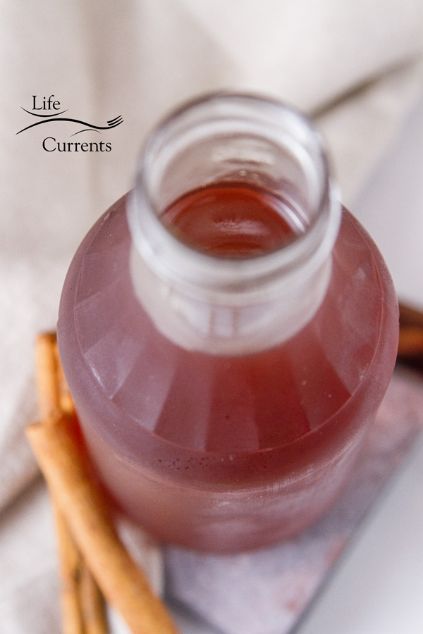 Looking down into a galss jar filled with cinnamon simple syrup with cinnamon sticks at the bottom of the picture