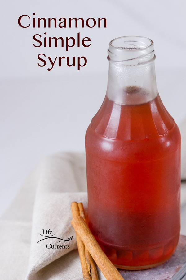 Cinnamon Simple Syrup in a glass jar with cinnamon sticks next to it near a grey cloth napkin on a white background with a title