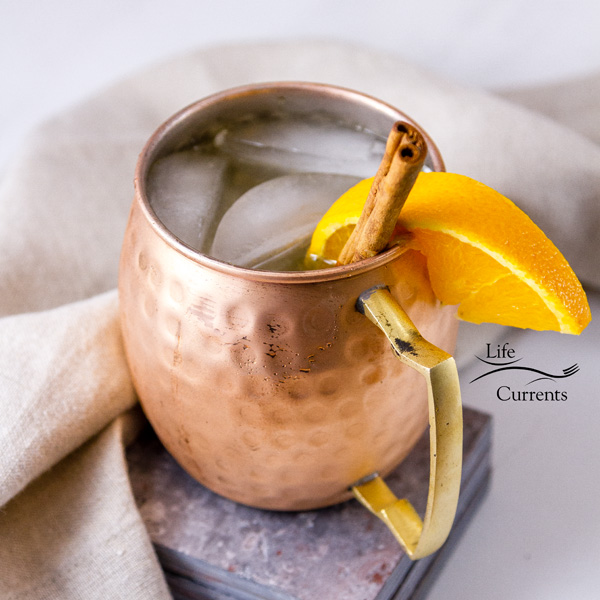 one copper mug filled with ice and a Moscow Mule drink garnished with an orange slice and a cinnamon stick on grey tile with a napkin and a white background
