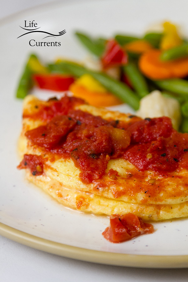 Breakfast: Veggie & Cheese Omelet with Fire-roasted Tomatoes on a white plate