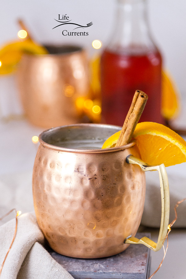 Copper mugs with orange and cinnamon garnishes with a bottle of cinnamon syrup in the background and twinkle lights around