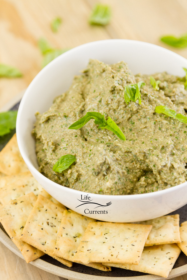 This Mushroom Walnut Pesto in a white bowl garnished with fresh basil leaves served with crackers