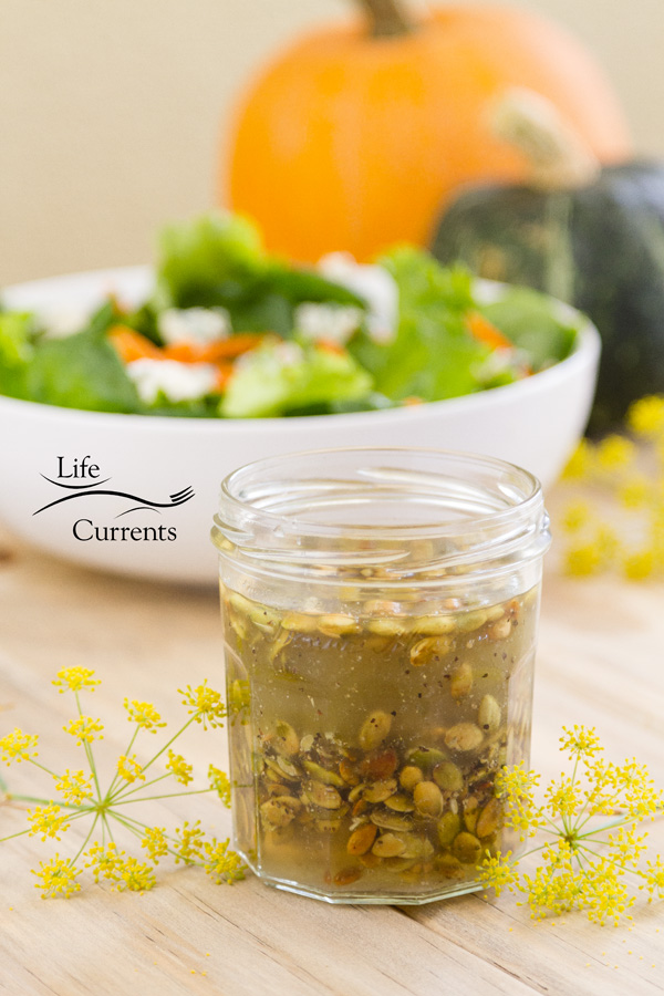 a jar of Toasted Pumpkin Seed Vinaigrette with a large white bowl full of green salad in the back. There are two pumpkins in the very back