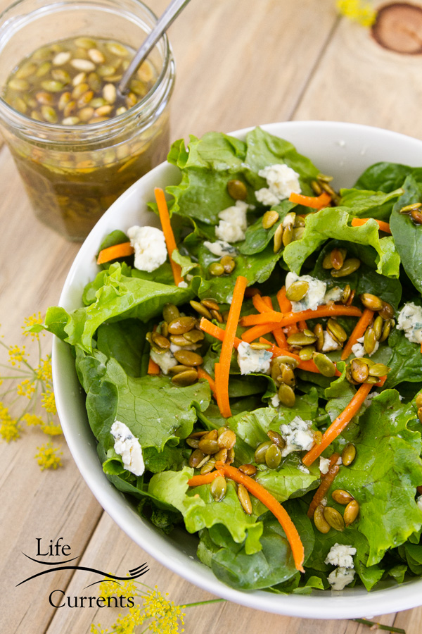 a green salad with lettuce, carrots, blue cheese crumbles, and Toasted Pumpkin Seed Vinaigrette with a jar of Toasted Pumpkin Seed Vinaigrette in the upper left and a spoon in the jar