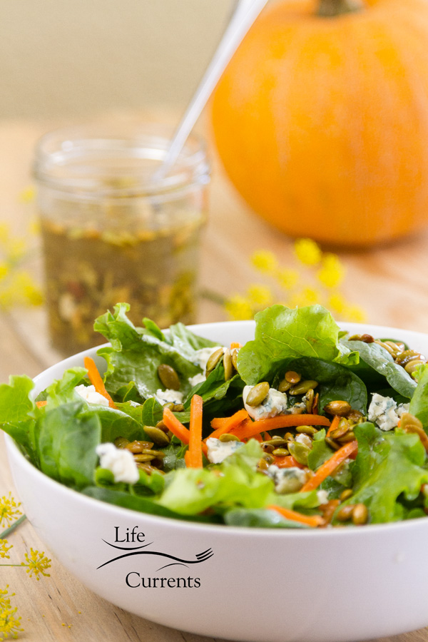 a green salad with a jar of Toasted Pumpkin Seed Vinaigrette and an orange pumpkin in the back
