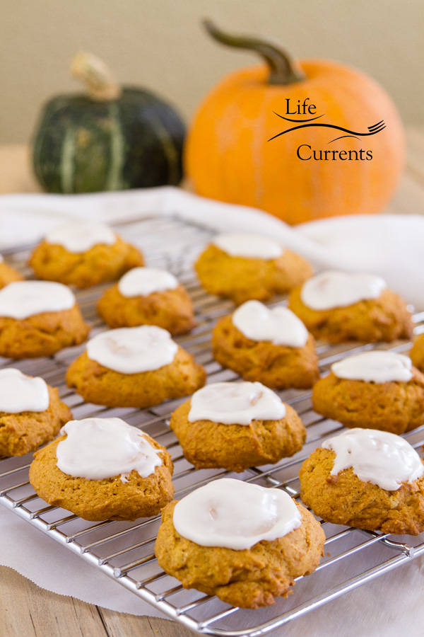 orange pumpkin cookies iced and cooling on a rack with a green and an orange pumpkin in the background