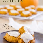 Pumpkin cookies on a black plate in front of a cooling rack of cookies with a pumpkin in the background