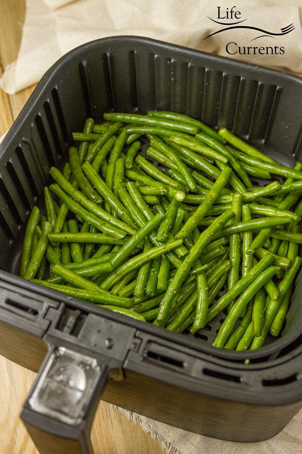 raw cleaned green beans in the basket of th eair fryer ready to be cooked