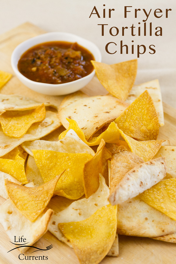 a pile of crispy tortilla chips cooked in the air fryer served with salsa