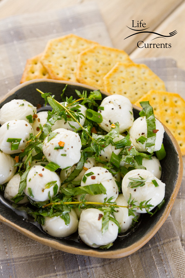 mozzarella and herbs in oil in a dark bowl served with crackers