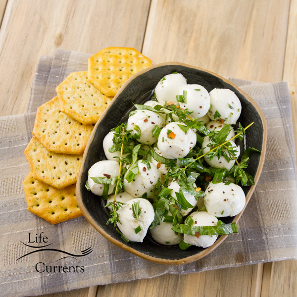 top down or flat lay photo of marinated mozzarella in a dark bowl served with crackers