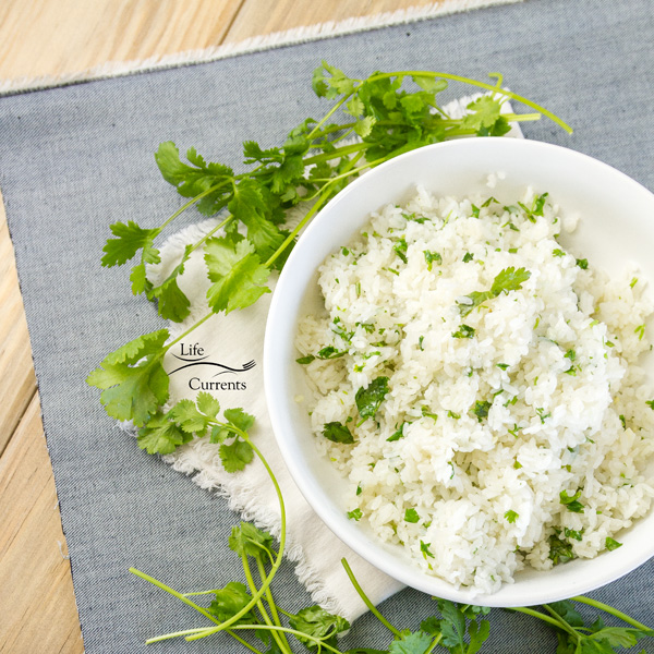 top down view of a white bowl with cilantro rice on a blue cloth with a white napkin and cilantro stems