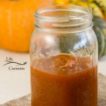 pumpkin butter in a jar in front of squashes