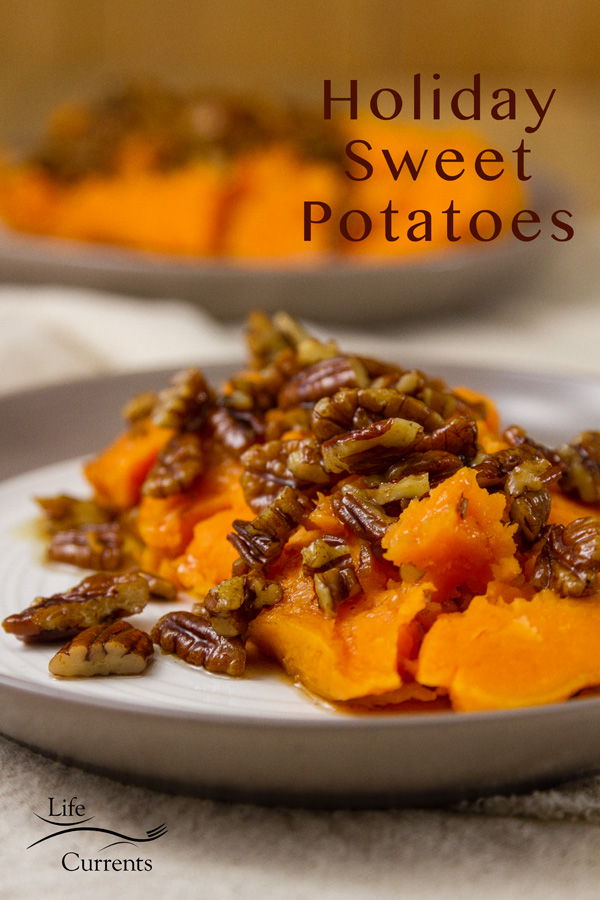 two baked sweet potatoes halves on two plates with maple brown butter pecan sauce