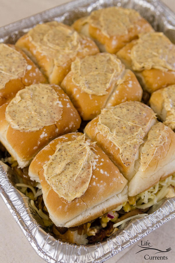 Carnitas Sliders: Top all of those layers with the bread tops, and smear the spiced butter over the top