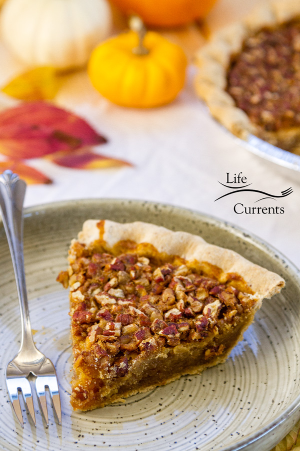 A piece of Bourbon Pecan Pie on a plate with a fork and some pumpkins in the background