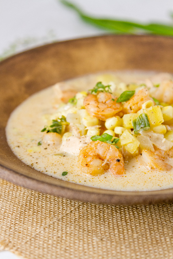 a brown bowl filled with seafood chowder - shrimp, corn, potatoes, tuna, green onions, on a brown background