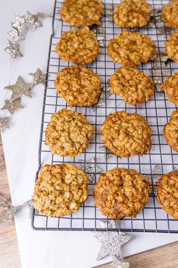 a rack of oatmeal cookies with silver glitter stars behind