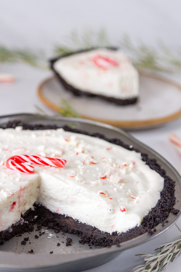 Candy cane pie with a slice taken out, the slice is in the background with a bite missing