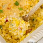 Creamed Corn in a servings dish with a wooden spoon