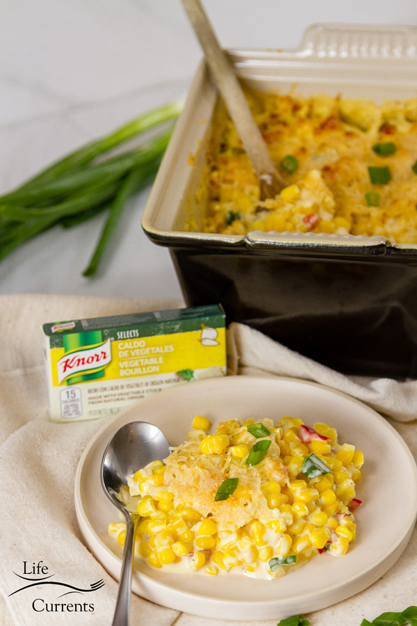a serving of corn side dish on a plate with a box of Knorr and the creamed corn in the background with some green onions