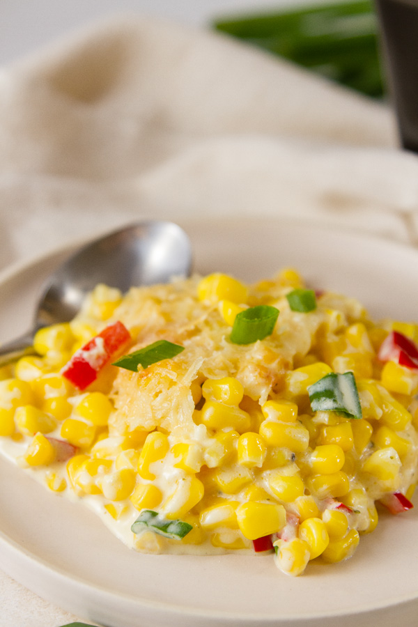 A seving of creamed corn on a plate with a spoon