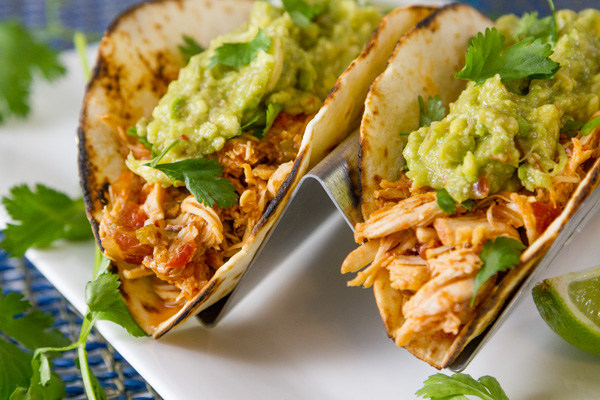 two tortillas filled with shredded chicken and guacamole topped with cilantro