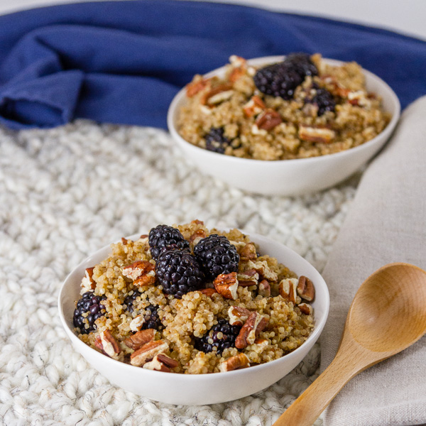 two servings of Breakfast Quinoa Bowl with Blackberries on a white cloth with a blue napkin in the back