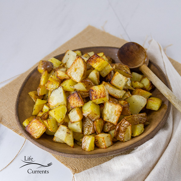 Square crop of Sheet Pan Roasted Potatoes in a brown bowl with a spoon