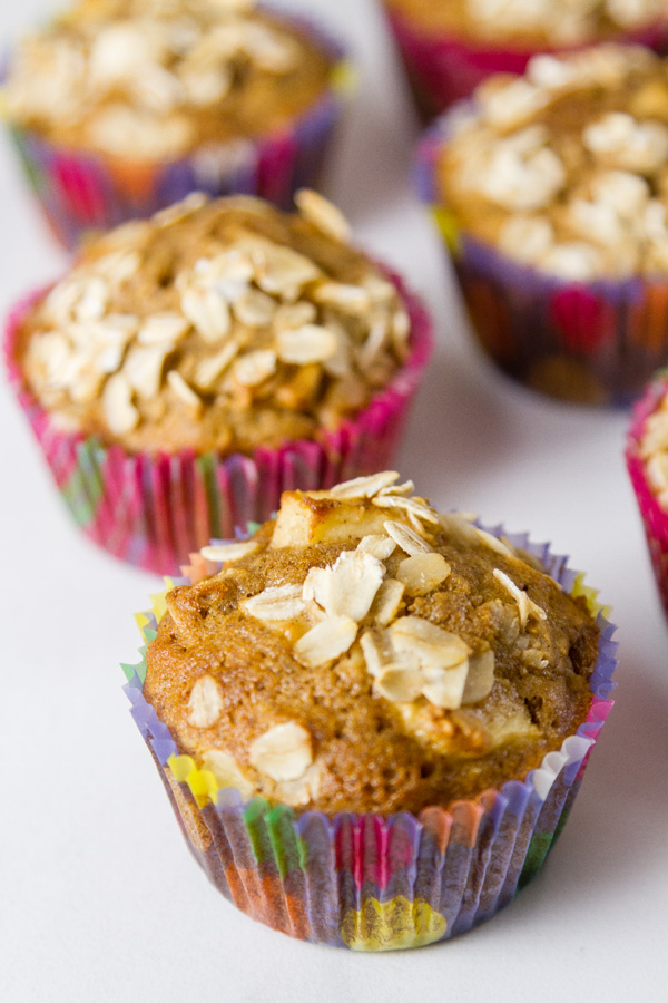 Apple oatmeal muffins in colorful liners on a white background