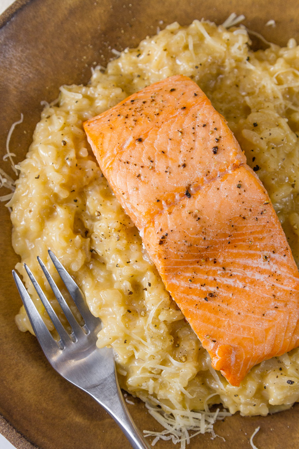 Roasted Salmon Risotto with a fillet of salmon over the risotto on a brown plate