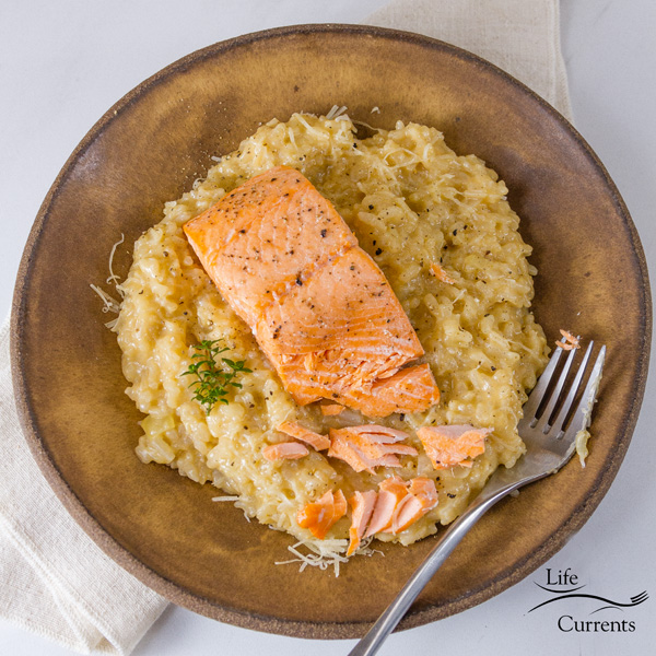 square crop of Roasted Salmon Risotto on a brwon plate with a fork