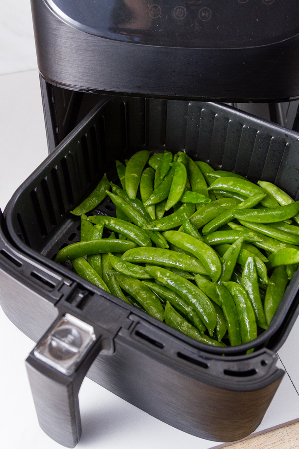 raw snap peas in the basket of the air fryer for Air Fryer Parmesan Sugar Snap Peas