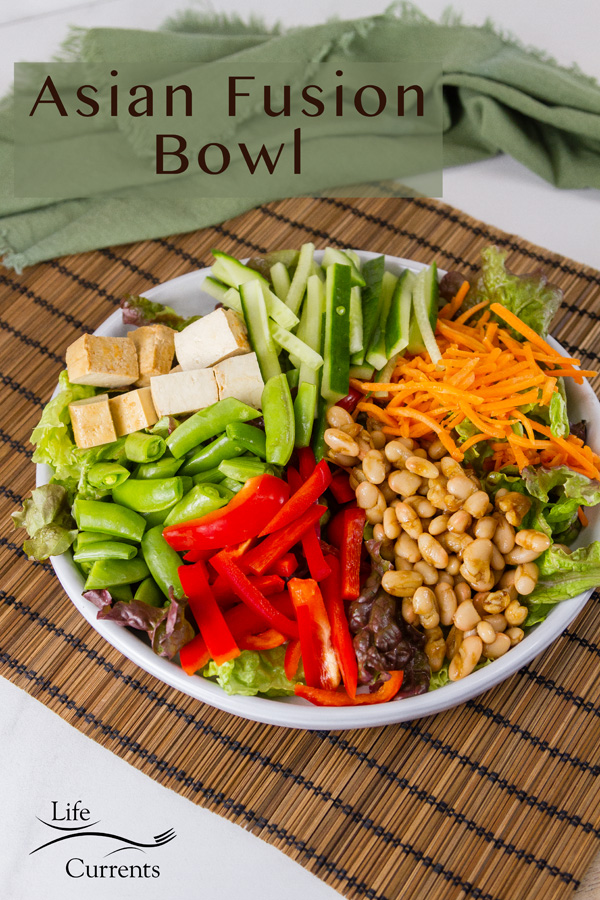 Asian Fusion Bowl Salad with lots of veggies, beans, tofu in a white bowl on a bamboo mat with a green napkin