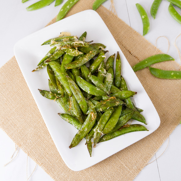 square crop of Air Fryer Parmesan Sugar Snap Peas on a white plate with brown fabric in back